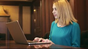 Beautiful woman using laptop and typing text on keyboard in home office. Beautiful woman using laptop and typing text on keyboard. Young woman working on stock footage