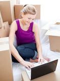 Beautiful woman using a laptop while unpacking box Stock Photography
