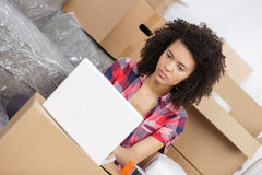Beautiful woman using laptop while unpacking box at home Royalty Free Stock Image