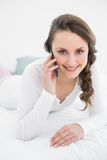Beautiful woman using mobile phone in bed Stock Image