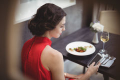 Beautiful woman using mobile phone while having meal Stock Photos
