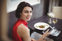 Beautiful woman using mobile phone while having meal Stock Photo