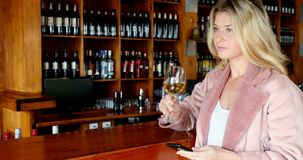 Beautiful woman using mobile phone while having wine 4k. Beautiful woman using mobile phone while having wine in bar 4k stock footage