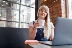 Young girl at cafe drinking coffee and using mobile phone. Online shopping. Beautiful woman using mobile phone and laptop while sitting at cafe. Young girl at stock images