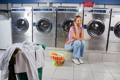 Beautiful Woman Using Mobile Phone At Laundry Stock Photos