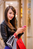 Beautiful woman using a mobile phone outside a shop Stock Images