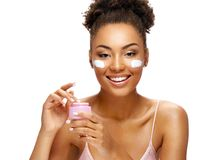 Beautiful woman using moisturizing cream. Photo of smiling african american woman on white background. Skin care and beauty concept stock image