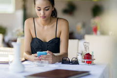 Beautiful woman using phone while waiting for meal in restaurant. Beautiful woman using phone in restaurant stock photo