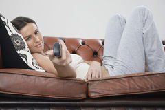 Beautiful Woman Using Remote Control While Lying On Sofa Royalty Free Stock Photography