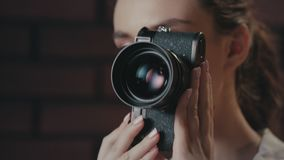 Beautiful woman using retro photo camera. Girl photographer working in studio stock video footage