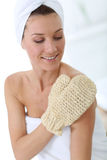Beautiful woman using rubbing gloves. Portrait of beautiful woman using rubbing glove Royalty Free Stock Photography