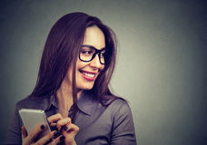 Beautiful woman using smart phone looking away laughing Stock Images