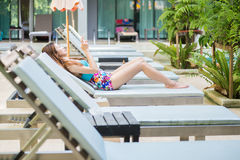 Beautiful woman using a smart phone on lounger near swimming poo Royalty Free Stock Photography