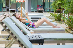 Beautiful woman using a smart phone on lounger near swimming poo Royalty Free Stock Photos