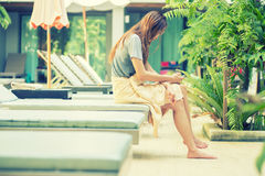 Beautiful woman using  smart phone on lounger near swimming pool Royalty Free Stock Photo