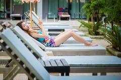 Beautiful woman using  smart phone on lounger near swimming pool Stock Image