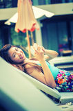 Beautiful woman using  smart phone on lounger near swimming pool Royalty Free Stock Images