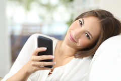 Beautiful woman using a smart phone. Sitting on a comfortable couch at home and looking at camera Royalty Free Stock Photo