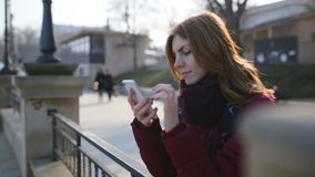 Beautiful woman using smart phone technology app in city streets at cold sunny day. In Odessa stock footage