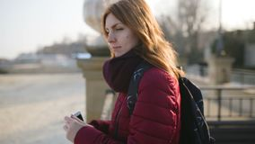 Beautiful woman using smart phone technology app in city streets at cold sunny day. Odessa stock video footage