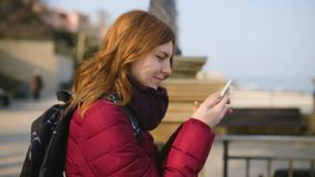 Beautiful woman using smart phone technology app in city streets at cold sunny day. In Odessa stock video footage