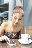 Beautiful woman using smart phone in the terrace reataurant. Stock Images