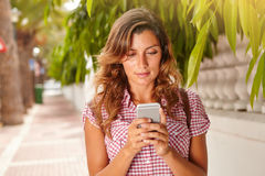 Beautiful woman using a smart phone for texting Stock Images