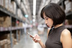 A beautiful woman using smart phone at the warehouse royalty free stock photos