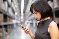 A beautiful woman using smart phone at the warehouse royalty free stock photo