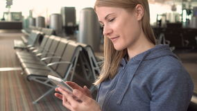 Beautiful woman using smartphone in airport. Browsing internet, communicating with her friends. Beautiful attractive young woman using smartphone in waiting stock video