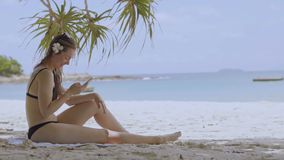 Beautiful woman using smartphone at the beach of tropical island. stock footage