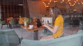 Freelancer woman using smartphone laptop in cafe texting sharing on social media stock video
