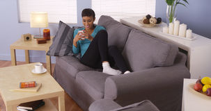 Beautiful woman using smartphone on couch Stock Photography
