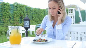 Beautiful woman using smartphone and eating salad in cafe.  stock footage