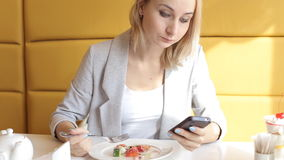 Beautiful woman using smartphone and eating salad in cafe in city.  stock video footage