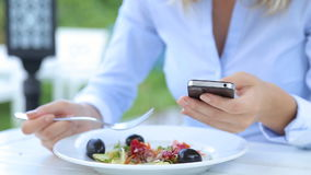 Beautiful woman using smartphone and eating salad in cafe in city.  stock footage