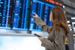 Woman using smartphone with flight information board at airport stock photos