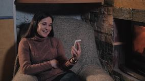 Beautiful Woman Using Smartphone Sitting By Fireplace at Home, Holiday And Lifestyle Concept stock video footage