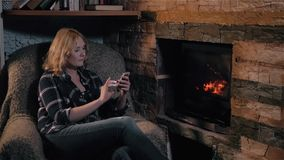 Beautiful Woman Using Smartphone Sitting By Fireplace at Home, Holiday And Lifestyle Concept stock footage