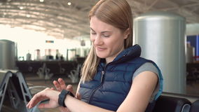Beautiful woman using smartwatch in airport. Browsing internet, communicating with her friends. stock video footage