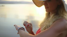 Beautiful woman using smartwatch checking messages. Tourist making gestures on a wearable touchscreen device. Close-up smart watch on female wrist stock footage