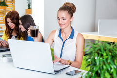 Beautiful woman using tablet computer and drinking her morning coffee. Business, technology and green office concept - young successful businesswoman with Royalty Free Stock Images