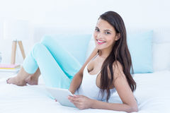 Beautiful woman using tablet pc on her bed Stock Photography