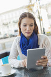 Beautiful woman using tablet PC at sidewalk cafe Royalty Free Stock Images