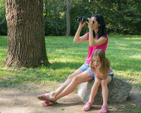 Beautiful woman and very bored girl looking through binoculars. Mother and her daughter looking through binoculars in the park Royalty Free Stock Image