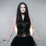 Beautiful woman with very long hair. On a gray background Stock Photos