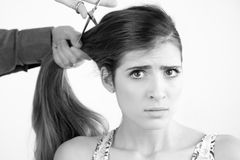 Beautiful woman with very long hair at saloon worried while getting haircut Royalty Free Stock Photos
