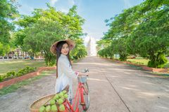 Beautiful woman with Vietnam culture tranditional dress. Ao dai and riding bicycle Royalty Free Stock Photography