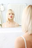 Beautiful woman viewing herself in the mirror stock images