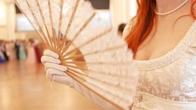 Beautiful woman in vintage ball costume woman waving a fan. Close up stock footage